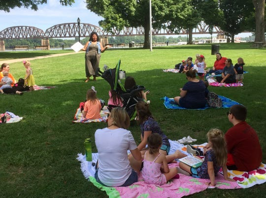 "Henderson County Public Library Children's Services Director Danielle Anguish leads Thursday mornings ""Reading in the Park"" program on the Riverfront Thursday in Audubon Mill Park."