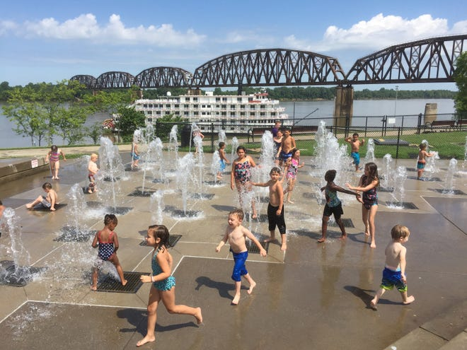 In this July 2019 file photo, children — most of them from Just For Kids Childcare on Third Street — beat the heat in the Henderson riverfront's splash pad with the Queen of the Mississippi docked in the background.