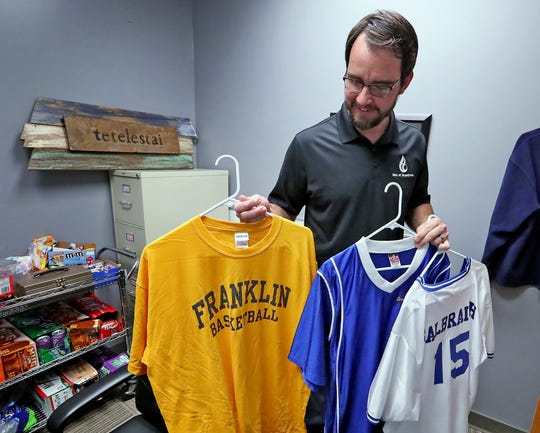 Brandywine Community Church Pastor of Student Ministries and Missions Paul Galbraith shows some of his high school and college sports T-shirts and jerseys.