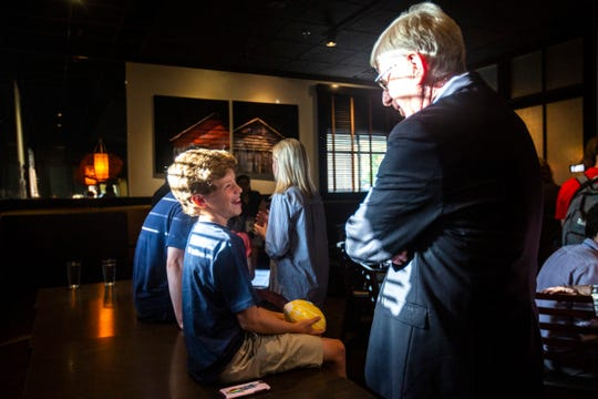 Cameron Bullock, 12, son of Montana Gov. Steve Bullock, talks with Iowa Attorney General Tom Miller, right, after a meet and greet, Wednesday, July 10, 2019, at BlackStone in Iowa City, Iowa.