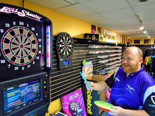 Store Manager Aaron Oehring talks about golf discs with customers in front of high-tech electronic dart boards at Darts & More, a new sports niche store which opened recently in North Liberty.