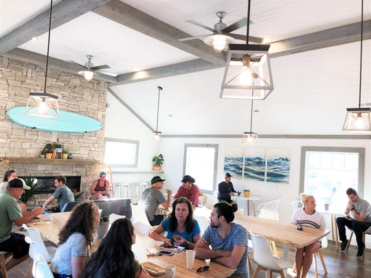 "Customers packed into the new Mahalo Coffee Roasters on opening day, July 6, 2019. ""We have seen so many coffee shops with community tables and we wanted to create that environment,"" said Trevor Bayne, owner of Mahalo Coffee Roasters."