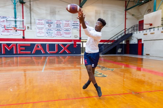 """Comeaux High senior running back Eddie Flugence goes for a catch in the Comeaux High School Gym. Head coach Doug Dotson said Flugence is """"the unsung hero"""" of the Spartans."""
