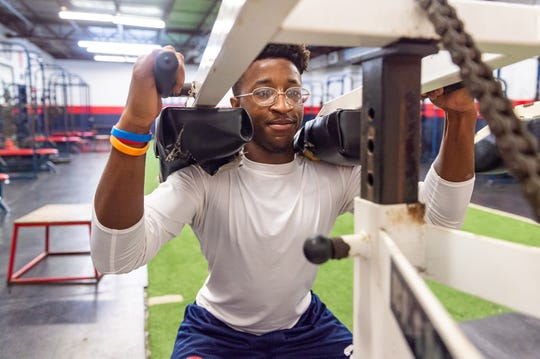 Eddie Flugence works out in the weight room at Comeaux High School.