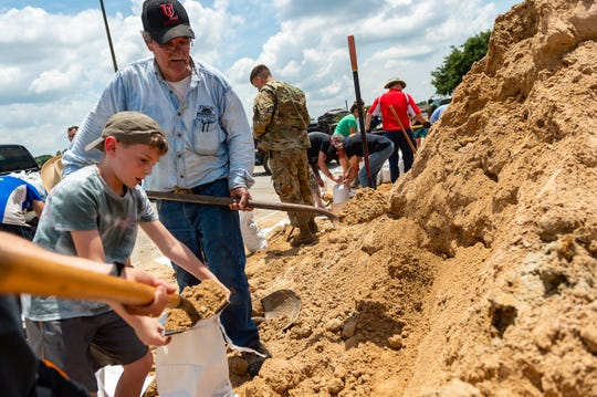 Residents prepare for heavy rainfall  by filling sandbags at Cajun Field Thursday.