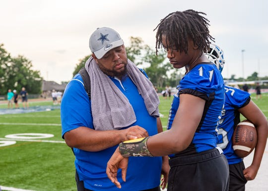 Head Coach Jacobi Thiery talking with quarterback Aaron Johnson - North Central Football at the Quick Slants All Acadiana 7 on 7 High School Football Tournament. Wednesday, July 10, 2019.