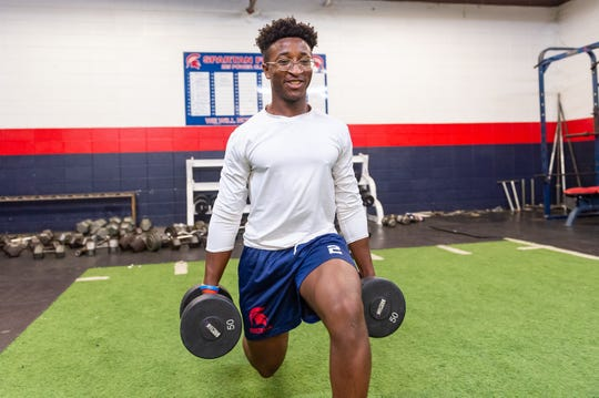 Comeaux High Spartans running back Eddie Flugence performs weighted walking lunges at Comeaux High. Head football coach Doug Dotson considers Flugence to be the Spartans' best offensive player pound-for-pound.