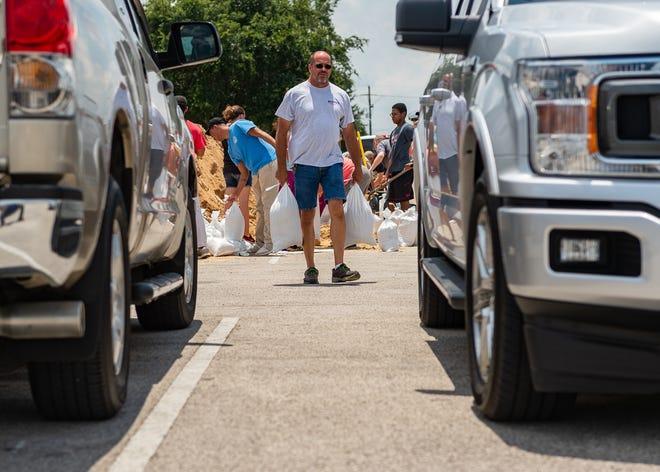 Residents prepare for heavy rainfall  by filling sandbags at Cajun Field Thursday.