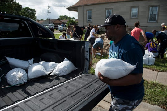 Devontee Alexis loads sandbags in the St. Roch neighborhood in New Orleans, La., on Thursday, July 11, 2019.