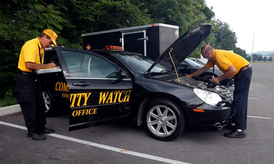 William Pohl, left, and Ronald Walker check a Fairfield County Sheriff's Office Community Watch cruiser Thursday morning, July 11, 2019, before taking it on patrol in the central part of the county. Pohl and Walker have been volunteers with the program for about three years. Community Watch members patrol county roads, direct traffic at crash scenes and help drivers that have been locked out of their cars.