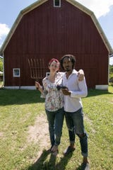 """In a nod to the """"American Gothic"""" painting, Erin and Elijah Hamilton pose in front of their Howell-based barn Thursday, July 11, 2019. On their farm, they raise goats and animate video game characters."""