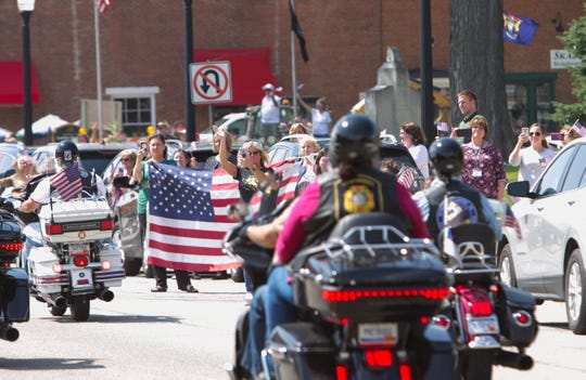 As trucks carrying traveling war memorials and a motorcycle escort drive through downtown Howell Wednesday, July 10, 2019, residents wave flags showing their patriotism.