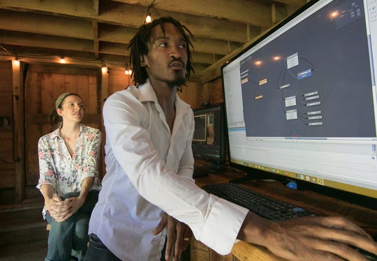 Elijah Hamilton shows the basic programming flow of a simple movement of an animated video character Thursday, July 11, 2019 with wife and partner Erin Hamilton in a barn on their farm in Howell. The couple founded Mitten Pixels, a game design and development company.