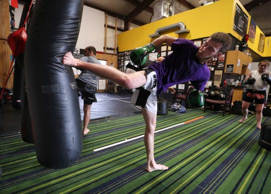 MMA fighter Lance Lawrence warms up before a training session at the Apex Martial Arts Academy in Bullitt County.  He is preparing for an upcoming match that could qualify him for a UFC contract if he wins. June 26, 2019