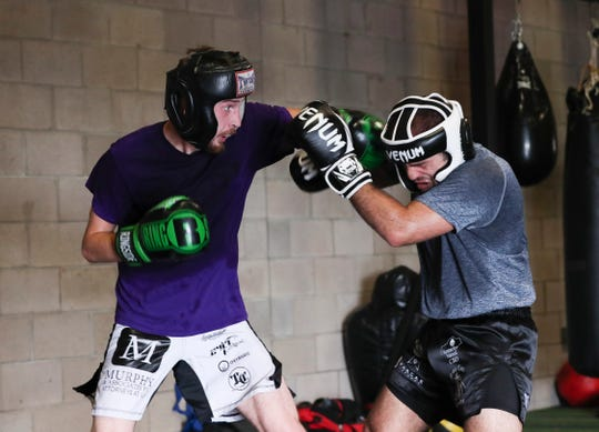 MMA fighter Lance Lawrence, left, lands a punch as he spars against Jamal Mohammed at the Apex Martial Arts Academy in Bullitt County. He is preparing for an upcoming match that could qualify him for a UFC contract if he wins.  June 26, 2019
