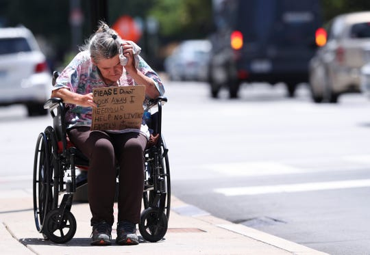 Linda Wood wipes sweat from her forehead as she asks for money at the corner of Third Street and Broadway on Thursday. She said she is waiting for her disability to be approved and is trying to avoid homelessness in the meantime.  July 11, 2019