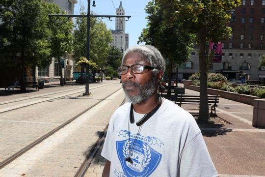 Earl Wilson poses for a portrait along Main Street downtown on Thursday, July 11, 2019. Wilson is a recent graduate of Manhood University, a six-week city-run program aimed to equip men with life skills like financial literacy, conflict resolution and time management, and has recently been hired on with the city's sanitation department, partly because of his training from the program.