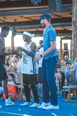 Eric Bledsoe (white jersey) shakes hands with Alex Antetokounmpo, and Brook Lopez (right) also joined the fray during a charity event in Greece.