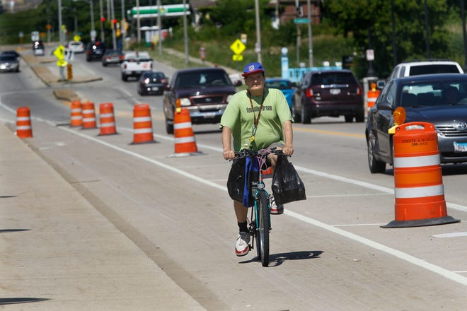 James Papp of Milwaukee bikes to a doctor's appointment on Thursday eastbound on the North Avenue bridge. Papp uses the bike lane on North Avenue. The city put permanent dividers on the bridge to separate bike and car lanes. Cars ran over all these dividers and now orange barrels are the only things separating the lanes. Cars have continued to dent and knock over the barrels.