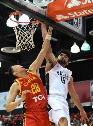 Bucks guard Elijah Bryant goes up for a basket against Chinese National Team center Shen Zijie during Summer League action Wednesday night in Las Vegas.