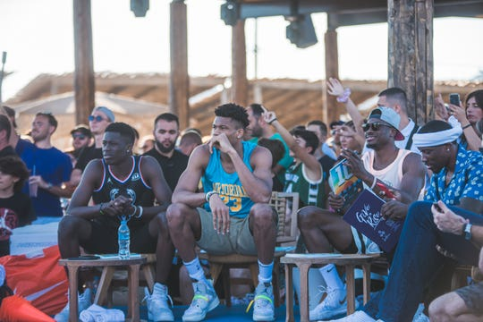 Giannis Antetokounmpo sits center flanked by his brothers Alex (left) and Thanasis, judging a dunk contest during the Give n Rise charity event in Greece.