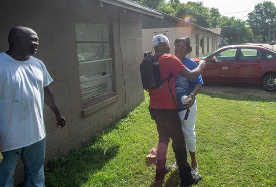 Columbus Cook hugs his sister outside their old family apartment on Wetumpka's Micanopy Street on Saturday, July 6, 2019.