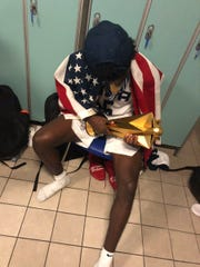 Team USA guard Kira Lewis of Alabama sits in front of his locker looking at the trophy for winning the FIBA 2019 Men's Basketball Under-19 World Cup championship in Greece on July 7, 2019. (Courtesy photo)