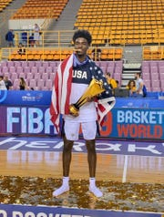 Team USA guard Kira Lewis of Alabama smiles with the gold medal in his teeth and the trophy after winning the FIBA 2019 Men's Basketball Under-19 World Cup championship in Greece on July 7, 2019. (Courtesy photo)