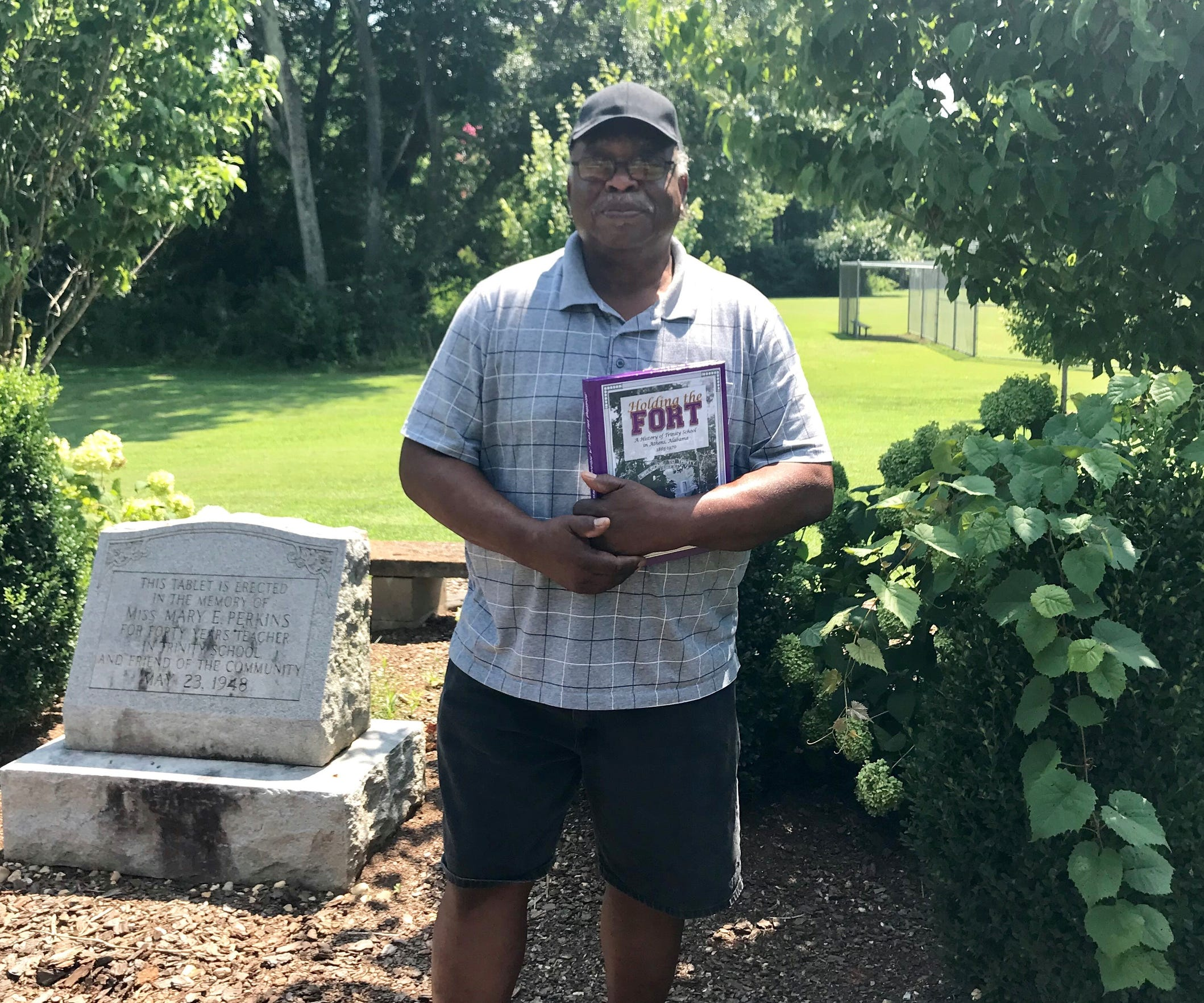 David Malone, a supporter of reparations whose ancestors were slaves in northern Alabama, stands at a memorial at the only black school in Limestone County for decades after the Civil War.