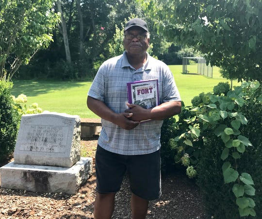 David Malone, a supporter of reparations whose ancestors were slaves in northern Alabama, stands at a memorial at the only black school in Limestone County for decades after the Civil War, which he is helping to preserve.