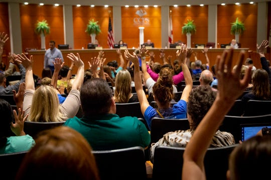 Meeting attendees wave their hands in lieu of clapping after listening to public comments during a special School Board meeting at the Collier County School District office in Naples on Thursday, July 11, 2019.