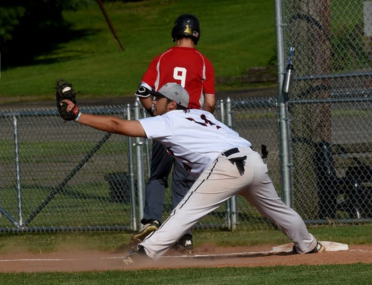 Coshocton Post 65 first baseman Dakoda Williamson stretches for the throw as Utica Post 92 runner Kaden Poorman attempts to beat the play. Coshocton defeated Utica 11-9 on Wednesday, July 10, 2019 at Coshocton Lake Park.