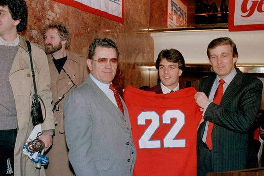 Boston College quarterback Doug Flutie poses with New Jersey Generals head coach Walt Michaels, left, and General's owner, Donald Trump, at a news conference in New York, Feb. 5, 1985. Michaels died Wednesday, July 10, 2019, his daughter announced Thursday.