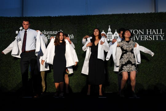 Class of 2019 White Coat Ceremony at Hackensack Meridian School of Medicine at Seton Hall University in Nutley on Thursday, July 11, 2019. (from left) Ryan Cassidy, Christina Caviasco, Seo Youn Chang and Alice Chang are presented with their white coats.