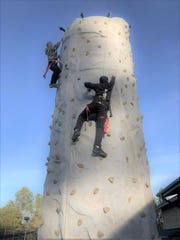 A race to the top as the two teens climb the new rock-climbing tower at Adventure Mountain on Mechem drive.