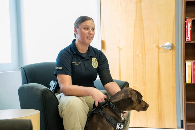 Maple, the Florida Department of Law Enforcement's first electronic storage detection K-9, sits with her handler, Stephanie Cassidy, Pensacola Special Agent with the FDLE, on Thursday.