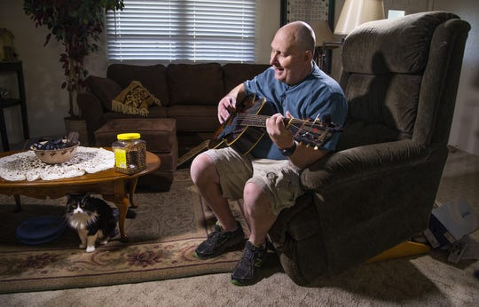 Jim Boerner, a U.S. Air Force veteran, may lose his Mesa home over a problem with his property tax payment. A guitar enthusiast, Boerner plays in his living room with his cat, Samantha on July 8, 2019.