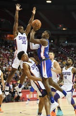 RJ Barrett of the New York Knicks is called for an offensive foul as he drives against Jalen Lecque (0) and Jack Salt (30) of the Phoenix Suns in NBA SUmmer League action.