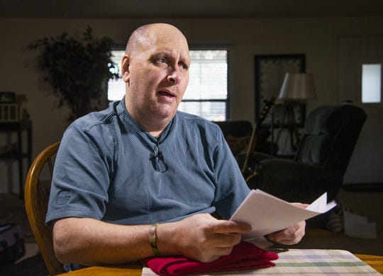 Jim Boerner, a U.S. Air Force veteran, may lose his Mesa home over a problem with his property tax payment. He looks at real estate documents on July 8, 2019.
