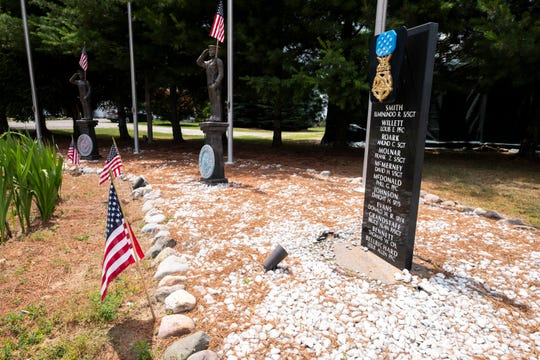 The names of Ron Zuccaro's friends are etched into a plaque beneath a Medal of Honor as part of the display in the front yard of his home on Connell Road, just outside of Yale.