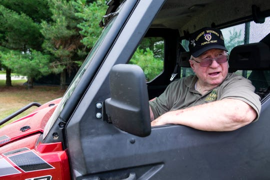 "Vietnam veteran Ron Zuccaro talks through the window of his Polaris Ranger Thursday, July 11, 2019, at his home on Connell Road just outside of Yale. This Saturday, Zuccaro is being honored by the National Society Sons of the American Revolution for his service and ""proud and patriotic"" display set up in his front yard."