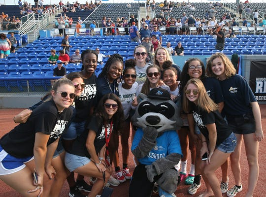 The FDR High School girls basketball team pose for a photo with Rascal at Champions Night at Dutchess Stadium in Fishkill on July 10, 2019.