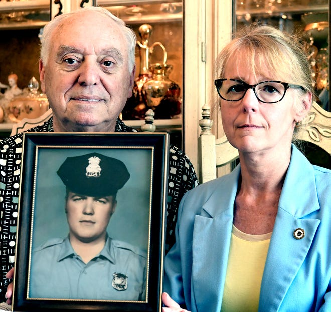 Henry Schaad's brother Barry, and daughter Sharon, pose with his portrait, at Barry's Windsor Township home Tuesday, July 9, 2019. Henry was a York City Police officer at the time of his murder during the '69 riots in York City. Bill Kalina photo