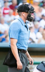 The umpire wears an ear piece to hear the call determined by the TrackMan radar system, July 10, 2019.