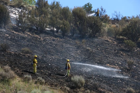 Crews battle a small brush fire above South McCarran Blvd near Caughlin Ranch in Reno on July 11, 2019.