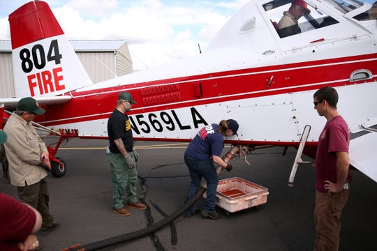 KJ DeGuire, a community wildfire forester with the Oregon Department of Forestry, practices attaching and removing a hose as she and other office employees train to load a single engine air tanker with fire retardant gel in preparation for wildfire season at the Salem Airport on July 11, 2019.