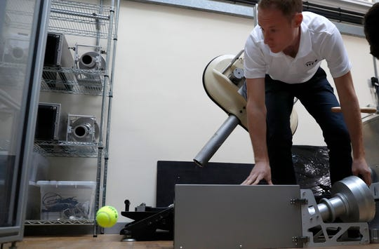 In this photo taken Friday June, 28, 2019, Jamie Caple-Davies, the head of the International Tennis Federation science and technical department, shows off a machine that tests the surface of a tennis court, during an interview with the Associated Press, at the International Tennis Federation (ITF) lab in Roehampton, near Wimbledon south west London. Based for about 20 years in a three-room area on what used to be a pair of squash courts in Roehampton, the ITF tech lab is filled with more than $1 million worth of machines that help make sure rules are followed and parameters are met.