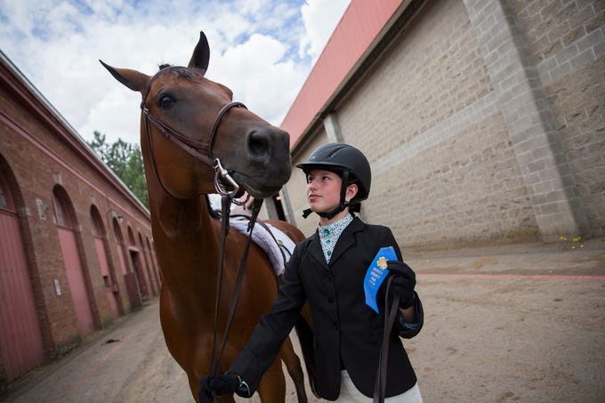 Tayler Kamm, of Turner, and her horse Banner are pictured after they won a blue ribbon during the opening day of the Marion County Fair at the Oregon State Fairgrounds in Salem on July 11, 2019.