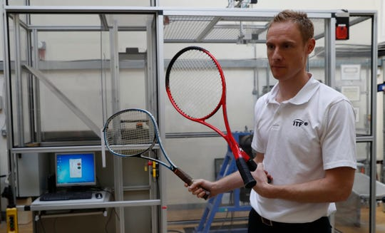 In this photo taken Friday June, 28, 2019, Jamie Caple-Davies, the head of the International Tennis Federation (ITF) science and technical department, holds up various designs of tennis racquets- both of which passed scrutiny by the ITF, at their lab in Roehampton, near Wimbledon south west London. Based for about 20 years in a three-room area on what used to be a pair of squash courts in Roehampton, the ITF tech lab is filled with more than $1 million worth of machines that help make sure rules are followed and parameters are met.
