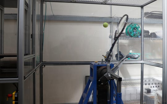 """In this photo taken Friday June, 28, 2019, a serve-simulating robot arm nicknamed """"Myo,"""" from the Greek word for """"muscle"""" is about to hit a ball dropped from above at the International Tennis Federation (ITF) lab in Roehampton, near Wimbledon south west London. Based for about 20 years in a three-room area on what used to be a pair of squash courts in Roehampton, the ITF tech lab is filled with more than $1 million worth of machines that help make sure rules are followed and parameters are met."""